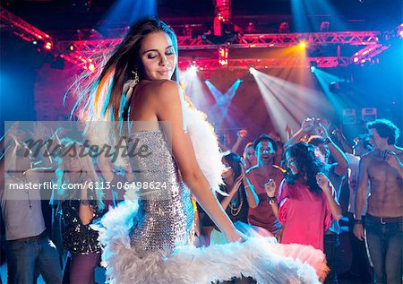 Woman in silver dress with feather boa dancing in nightclub Stock Photo - Premium Royalty-Free, Image code: 6113-06498624