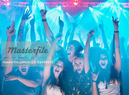 Portrait of enthusiastic crowd with arms raised at concert Stock Photo - Premium Royalty-Free, Image code: 6113-06498631