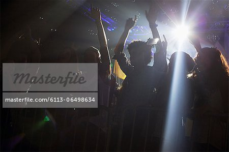 Spotlight above silhouette of crowd cheering at concert Stock Photo - Premium Royalty-Free, Image code: 6113-06498634
