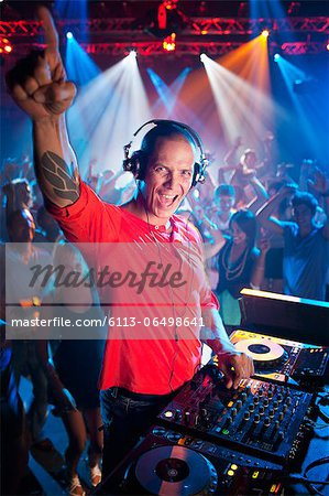 Portrait of enthusiastic DJ at turntable in nightclub Stock Photo - Premium Royalty-Free, Image code: 6113-06498641