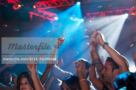 Enthusiastic crowd with arms raised on dance floor of nightclub Stock Photo - Premium Royalty-Free, Image code: 6113-06498643