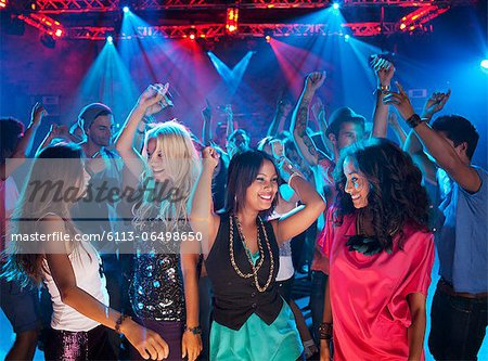Smiling friends dancing on dance floor of nightclub Stock Photo - Premium Royalty-Free, Image code: 6113-06498650