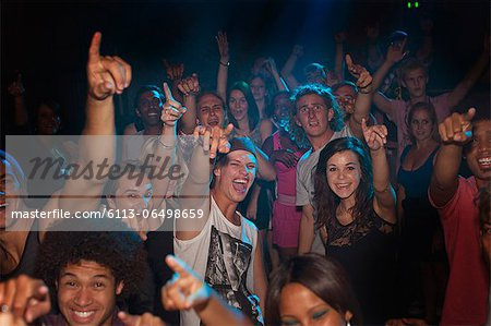 Enthusiastic crowd cheering at concert Stock Photo - Premium Royalty-Free, Image code: 6113-06498659