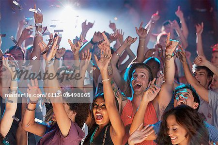 Enthusiastic crowd cheering at concert Stock Photo - Premium Royalty-Free, Image code: 6113-06498665