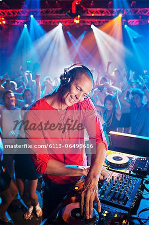 DJ at turntable with crowd on dance floor in background Stock Photo - Premium Royalty-Free, Image code: 6113-06498666