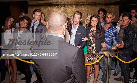 Crowd gesturing to bouncer behind rope outside night club Stock Photo - Premium Royalty-Free, Image code: 6113-06498667