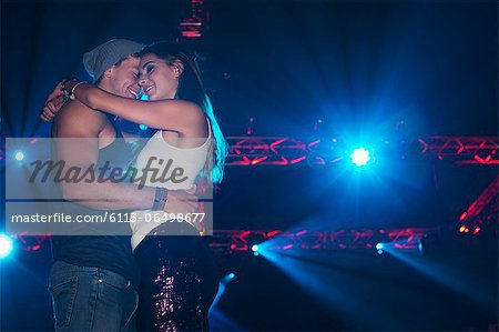 Smiling couple hugging under spotlights in nightclub Stock Photo - Premium Royalty-Free, Image code: 6113-06498677