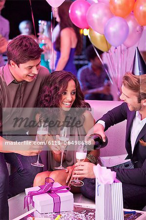 Smiling friends drinking champagne and celebrating birthday in nightclub Stock Photo - Premium Royalty-Free, Image code: 6113-06498688