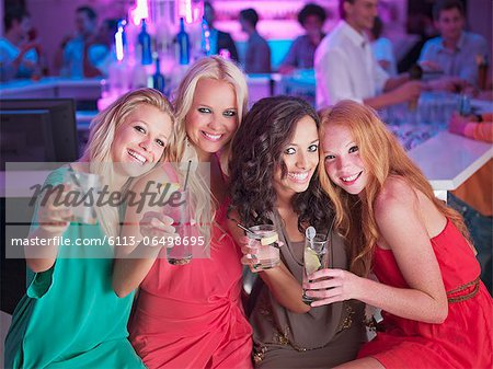 Portrait of smiling women with cocktails in nightclub Stock Photo - Premium Royalty-Free, Image code: 6113-06498695
