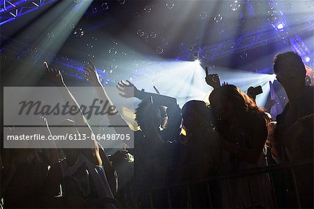 Crowd cheering with arms raised at concert