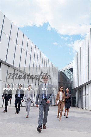 Confident business people walking outside building Stock Photo - Premium Royalty-Free, Image code: 6113-06498819