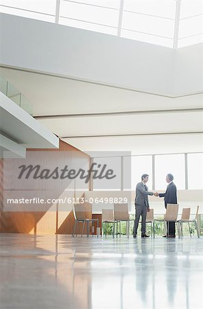 Businessmen shaking hands at circle of chairs in lobby Stock Photo - Premium Royalty-Free, Image code: 6113-06498829