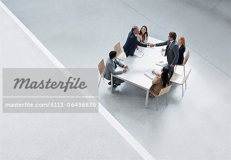 Businessmen in meeting shaking hands across table Stock Photo - Premium Royalty-Free, Image code: 6113-06498830