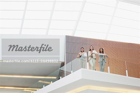 Portrait of smiling businesswomen standing on balcony in modern office Stock Photo - Premium Royalty-Free, Image code: 6113-06498832