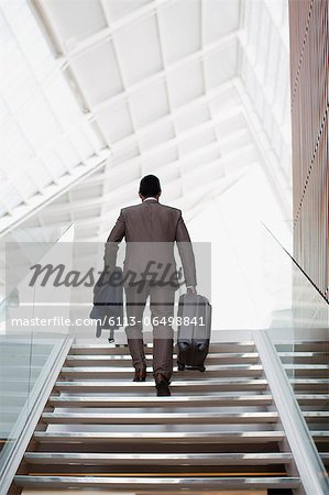 Businessman with suitcase ascending stairs Stock Photo - Premium Royalty-Free, Image code: 6113-06498841