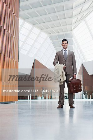 Portrait of smiling businessman holding coat and briefcase in lobby Stock Photo - Premium Royalty-Free, Image code: 6113-06498870