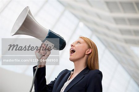 Businesswoman shouting into bullhorn Stock Photo - Premium Royalty-Free, Image code: 6113-06498900