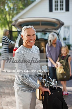 Older man carrying golf clubs in bag Stock Photo - Premium Royalty-Free, Image code: 6113-06499018