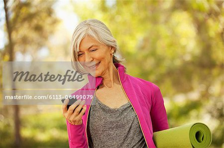Older woman using cell phone outdoors Stock Photo - Premium Royalty-Free, Image code: 6113-06499079