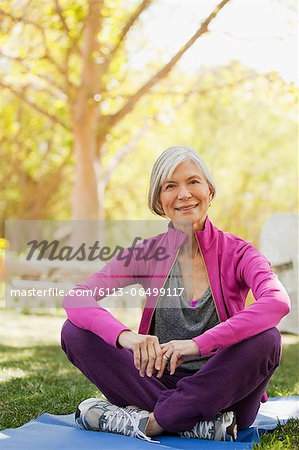 Older woman sitting on yoga mat outdoors Stock Photo - Premium Royalty-Free, Image code: 6113-06499117