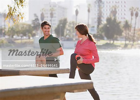 Couple stretching together in park Stock Photo - Premium Royalty-Free, Image code: 6113-06499141
