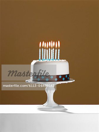 Birthday cake with lit candles on cake stand Stock Photo - Premium Royalty-Free, Image code: 6113-06499143