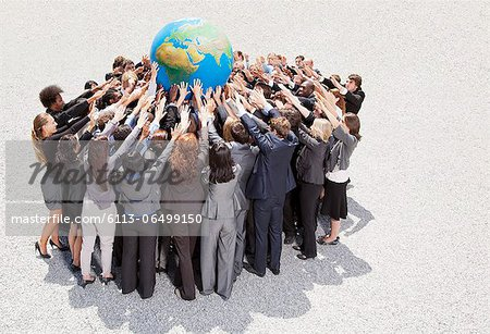 Crowd of business people in huddle reaching for globe Stock Photo - Premium Royalty-Free, Image code: 6113-06499150