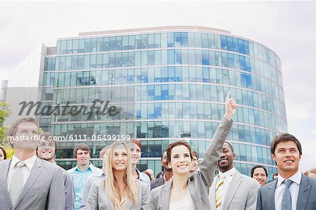Crowd of smiling business people in front of building Stock Photo - Premium Royalty-Free, Image code: 6113-06499159