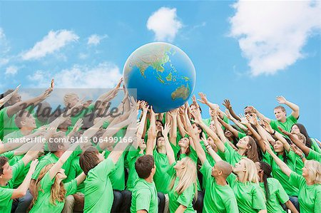 Team in green t-shirts lifting globe overhead Stock Photo - Premium Royalty-Free, Image code: 6113-06499166