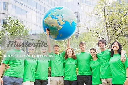 Portrait of team in green t-shirts lifting globe overhead Stock Photo - Premium Royalty-Free, Image code: 6113-06499185