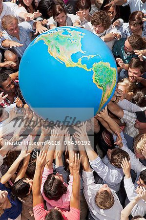 Crowd of people reaching for globe Stock Photo - Premium Royalty-Free, Image code: 6113-06499192
