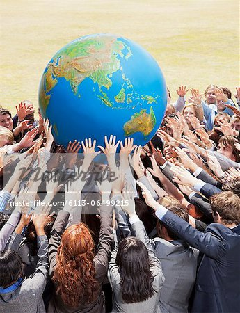 Crowd of business people reaching for globe Stock Photo - Premium Royalty-Free, Image code: 6113-06499215