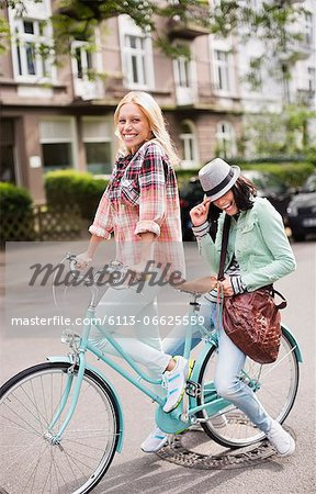 Women riding bicycle together on city street Stock Photo - Premium Royalty-Free, Image code: 6113-06625559