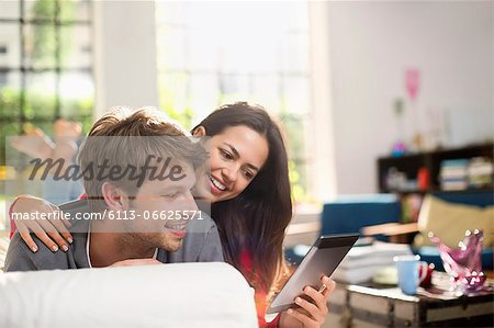 Couple using digital tablet on sofa Stock Photo - Premium Royalty-Free, Image code: 6113-06625571