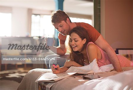 Couple reading newspaper together on bed Stock Photo - Premium Royalty-Free, Image code: 6113-06625574
