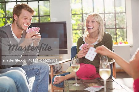 Friends playing card game in living room Stock Photo - Premium Royalty-Free, Image code: 6113-06625581