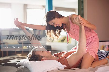 Smiling couple playing on bed Stock Photo - Premium Royalty-Free, Image code: 6113-06625603