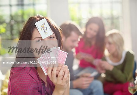 Smiling woman playing card game Stock Photo - Premium Royalty-Free, Image code: 6113-06625611