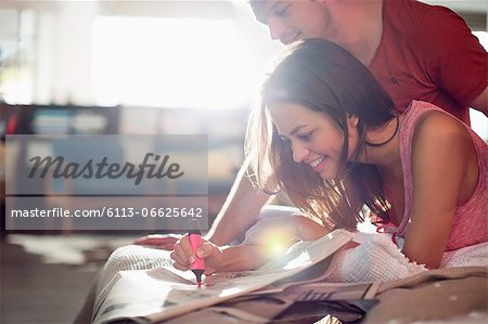 Couple reading newspaper together on bed Stock Photo - Premium Royalty-Free, Image code: 6113-06625642