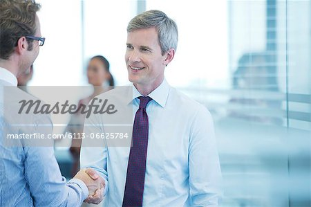 Businessmen shaking hands in office Stock Photo - Premium Royalty-Free, Image code: 6113-06625784