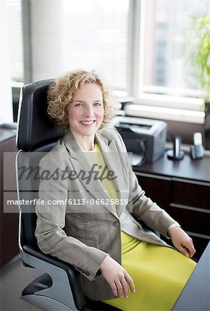 Businesswoman smiling at desk Stock Photo - Premium Royalty-Free, Image code: 6113-06625818