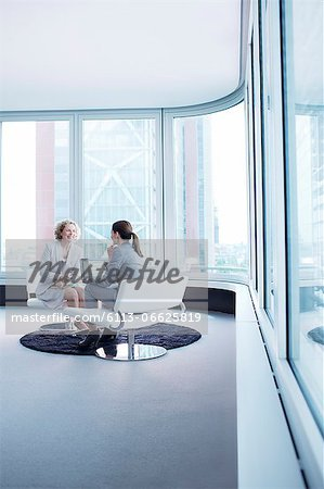 Businesswomen talking in office lobby Stock Photo - Premium Royalty-Free, Image code: 6113-06625819