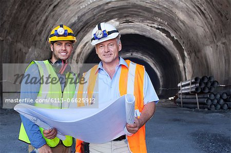 Workers reading blueprints in tunnel Stock Photo - Premium Royalty-Free, Image code: 6113-06625912