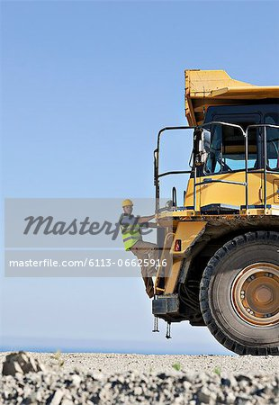 Worker climbing machinery in quarry Stock Photo - Premium Royalty-Free, Image code: 6113-06625916