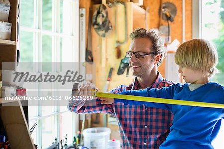 Father and son working in garage Stock Photo - Premium Royalty-Free, Image code: 6113-06626289