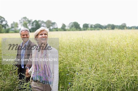 Couple walking in field of tall grass