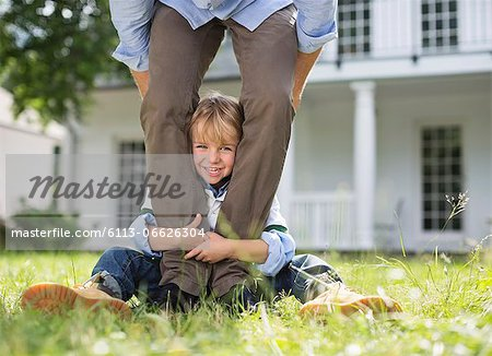 Boy peeking out from between father's legs Stock Photo - Premium Royalty-Free, Image code: 6113-06626304