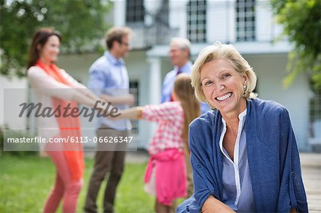 Smiling woman sitting outdoors Stock Photo - Premium Royalty-Free, Image code: 6113-06626347