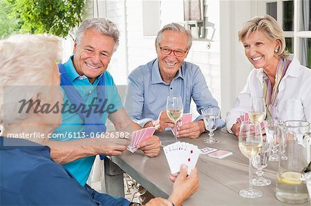 Friends playing card games at table Stock Photo - Premium Royalty-Free, Image code: 6113-06626382