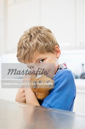 Boy cuddling guinea pig in vet's surgery Stock Photo - Premium Royalty-Free, Image code: 6113-06626486
